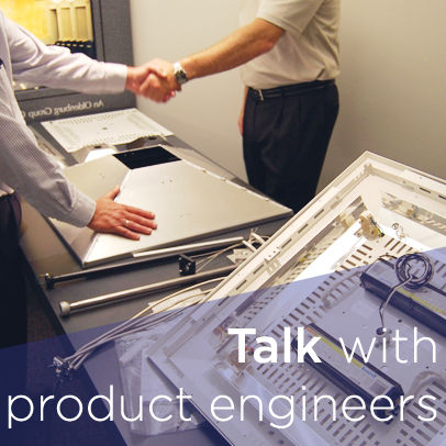 An engineer and a salesperson shake hands over a product table