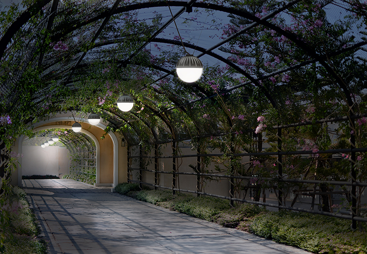 Zume outdoor pendants in a catenary lighting design under a vine-covered walkway